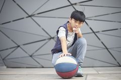 Retrato del niño asiático fresco que lleva a cabo baloncesto al aire libre Imagenes de archivo