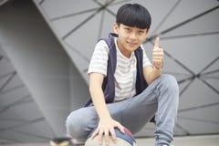 Retrato del niño asiático fresco que lleva a cabo baloncesto al aire libre Imagen de archivo