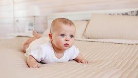 Retrato del niño bonito en la ropa blanca en una cama en casa almacen de metraje de vídeo