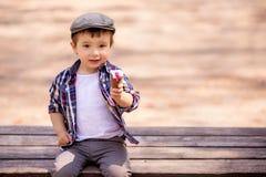 Retrato del niño de lujo del niño que se sienta en el banco al aire libre y que sostiene un helado que ofrece compartir el postre imagenes de archivo