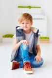 Retrato del niño de moda lindo, muchacho que se sienta en el piso Foto de archivo libre de regalías