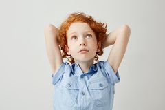 Retrato del niño hermoso con el pelo rizado anaranjado y las pecas que llevan a cabo las manos detrás de la cabeza, mirando la pa Fotografía de archivo libre de regalías