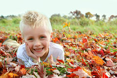 Retrato del niño joven feliz que pone en Autumn Leaves caido Fotografía de archivo libre de regalías