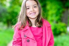 Retrato del niño lindo feliz que se coloca en un parque Imágenes de archivo libres de regalías
