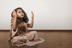 Retrato del niño musulmán asiático que se sienta en piso y que ruega Imagen de archivo libre de regalías