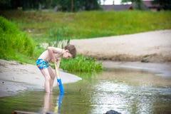 Retrato del niño pequeño caucásico en el sombrero de paja que juega los juguetes y la bomba de agua en la playa foto de archivo