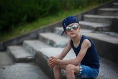 Retrato del niño pequeño de moda en gafas de sol y casquillo Childh Imágenes de archivo libres de regalías