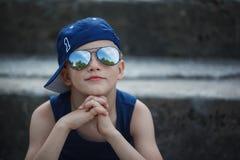 Retrato del niño pequeño de moda en gafas de sol y casquillo Childho Fotografía de archivo