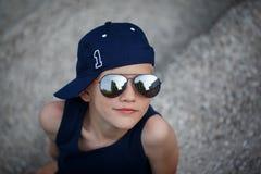 Retrato del niño pequeño de moda en gafas de sol y casquillo Niñez Foto de archivo libre de regalías