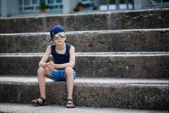 Retrato del niño pequeño de moda en gafas de sol y la localización del casquillo Fotos de archivo