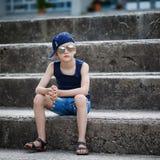 Retrato del niño pequeño de moda en gafas de sol y la localización del casquillo Fotografía de archivo libre de regalías