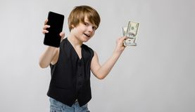 Retrato del niño pequeño emocionado divertido adorable que se coloca en estudio con el teléfono móvil y el dinero en sus manos en Foto de archivo libre de regalías