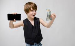 Retrato del niño pequeño emocionado divertido adorable que se coloca en estudio con el teléfono móvil y el dinero en sus manos en Fotografía de archivo