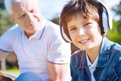 Retrato del niño pequeño en auriculares que sonríe en cámara Imagen de archivo