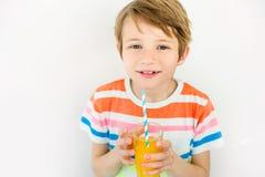Retrato del niño pequeño feliz que bebe el zumo de naranja Imagenes de archivo