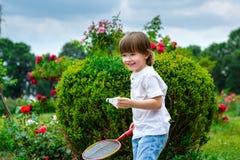 Retrato del niño pequeño feliz que lleva a cabo bádminton imagen de archivo