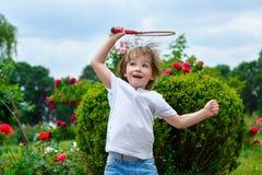 Retrato del niño pequeño feliz que lleva a cabo bádminton fotografía de archivo libre de regalías