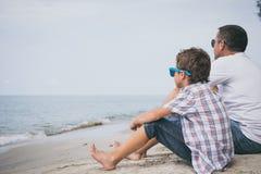 Retrato del niño pequeño joven y del padre tristes que se sientan al aire libre en Imágenes de archivo libres de regalías