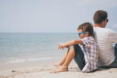 Retrato del niño pequeño joven y del padre tristes que se sientan al aire libre en Imagen de archivo libre de regalías