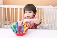 Retrato del niño pequeño que juega con los pernos de ropa Foto de archivo libre de regalías