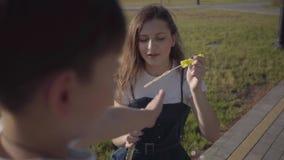 Retrato del niño pequeño que mira a su más vieja hermana en el parque que burbujas de jabón que soplan Hermanos lindos que pasan  almacen de metraje de vídeo