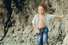Retrato del niño pequeño que se coloca en la playa Imágenes de archivo libres de regalías