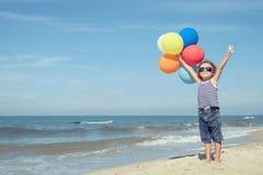Retrato del niño pequeño que se coloca en la playa en el tiempo del día Imagenes de archivo