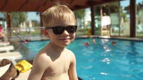 Retrato del niño pequeño sonriente con las gafas de sol en el fondo de la piscina, cámara lenta metrajes