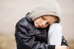 Retrato del niño pequeño triste que lleva la chaqueta de cuero y la capilla negras foto de archivo
