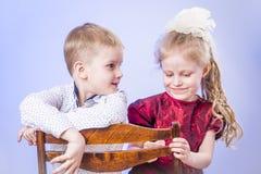 Retrato del niño pequeño y de la muchacha lindos en silla Imágenes de archivo libres de regalías