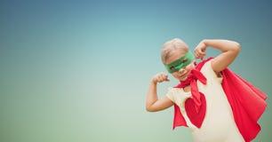 Retrato del niño que lleva el cabo rojo y la máscara verde que muestran los músculos contra el cielo claro Imágenes de archivo libres de regalías