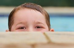 Retrato del niño que mira a escondidas sobre el borde de la piscina Fotografía de archivo libre de regalías