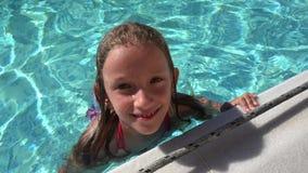 Retrato del niño que salpica el agua en la piscina, cara sonriente de la muchacha que baña 4K almacen de metraje de vídeo