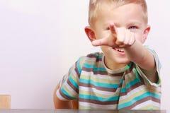 Retrato del niño rubio feliz del niño del muchacho que señala en usted en la tabla Fotos de archivo libres de regalías