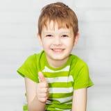 Retrato del niño sonriente que detiene su pulgar Imagen de archivo