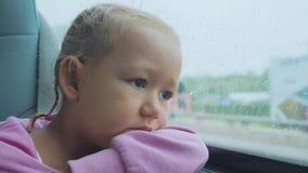 Retrato del niño triste que mira hacia fuera la ventana mojada, mientras que viaja en autobús almacen de metraje de vídeo