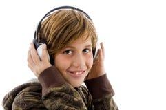 Retrato del niño sonriente que disfruta de música Foto de archivo