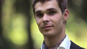 Retrato del novio hermoso joven en la naturaleza almacen de metraje de vídeo
