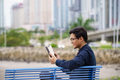 Retrato del oficinista asiático con el ipad en banco Fotos de archivo