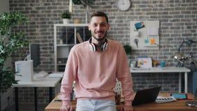 Retrato del oficinista hermoso del hombre joven que mira la cámara y la sonrisa almacen de metraje de vídeo