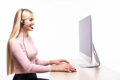 Retrato del operador de sexo femenino con las auriculares que sonríe en la cámara en centro de atención telefónica en blanco Fotografía de archivo libre de regalías