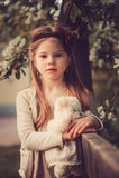 Retrato del país de la primavera de la muchacha soñadora adorable del niño cerca de la cerca de madera con el oso de peluche Foto de archivo libre de regalías