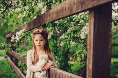 Retrato del país de la primavera de la muchacha soñadora adorable del niño cerca de la cerca de madera con el oso de peluche Imagen de archivo