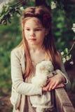Retrato del país de la primavera de la muchacha soñadora adorable del niño cerca de la cerca de madera con el oso de peluche Fotos de archivo libres de regalías