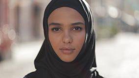 Retrato del pañuelo del hijab de la mujer que lleva musulmán joven hermosa que mira en la situación de la cámara en la ciudad vie almacen de video