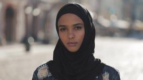 Retrato del pañuelo del hijab de la mujer que lleva musulmán joven hermosa que mira en la situación de la cámara en la ciudad vie almacen de metraje de vídeo