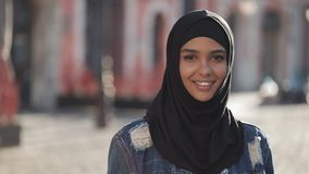Retrato del pañuelo del hijab de la mujer que lleva musulmán joven hermosa que sonríe en la situación de la cámara en la ciudad v almacen de video