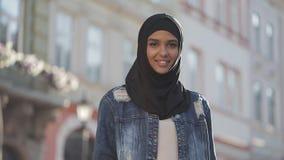 Retrato del pañuelo del hijab de la mujer que lleva musulmán joven hermosa que sonríe en la situación de la cámara en la ciudad v almacen de metraje de vídeo