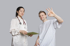 Retrato del paciente que gesticula muy bien con el doctor que sostiene un tablero Fotografía de archivo