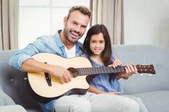 Retrato del padre feliz que toca la guitarra con la hija Imagen de archivo